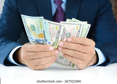 Businessman counting money,US dollar (USD) bills, on the table