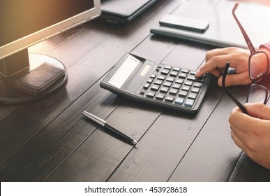 Businessman counting taxes sitting at office table