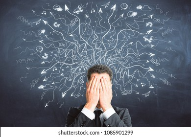 Businessman covering face on chalkboard background with drawn arrows. Risk and confusion concept