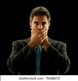 Businessman covering his mouth on black background.