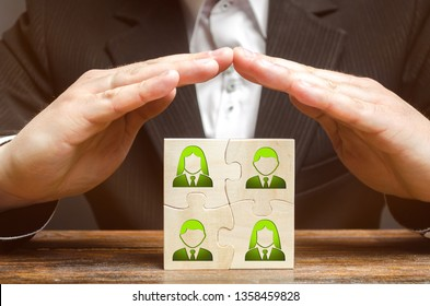 Businessman covers with hands the business team of employees. Patronage support, encouragement, privilege and financial aid. Government support smaller or local businesses. Team insurance, protection.