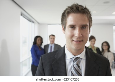 Businessman with co-workers in background