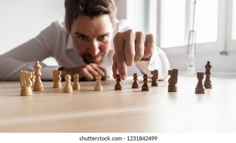 Businessman creating business strategy by arranging black and white chess pieces on  his office desk.