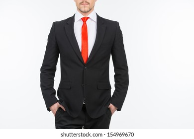 Businessman. Cropped image of bossy young men holding hands in pockets while standing isolated on white