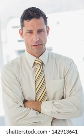 Businessman with crossed arms looking at camera in office