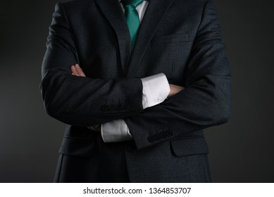 Businessman with a crossed hands on a gray background. Business acumen. Strict boss.