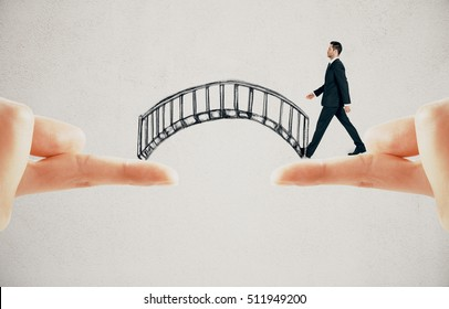 Businessman crossing abstract drawn bridge leading from finger to finger