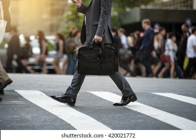 Businessman crossing the street on crosswalk and holding a laptop bag and smatphone in the city