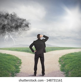 Businessman at a crossroads with storm and sunshine