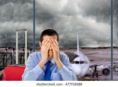 businessman crying by delayed flight because the stormy weather at the lobby airport