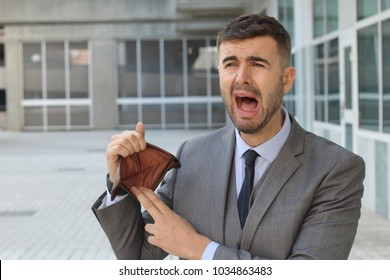 Businessman crying holding his empty wallet