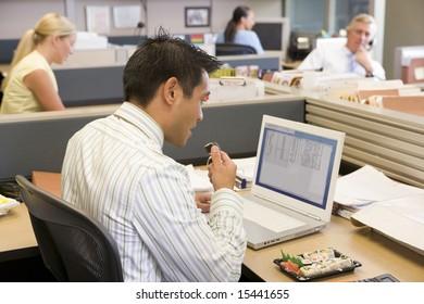 Businessman in cubicle at laptop eating sushi