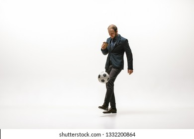 Businessman with a cup of coffee and football ball in office. Soccer freestyle. Concept of balance and agility in business. Manager perfoming tricks isolated on white studio background.