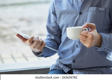 businessman with a cup of coffee and with the tablet at the window