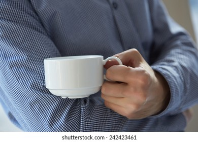 businessman with a cup of coffee at the window