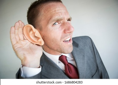 Businessman cupping his large ear straining to hear with a funny expression