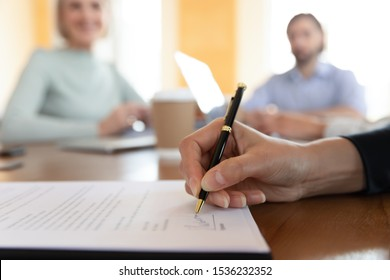 Businessman customer bank loan service buyer sign paper document at meeting, male client buy insurance get hired make business deal write signature on employment contract agreement, close up view