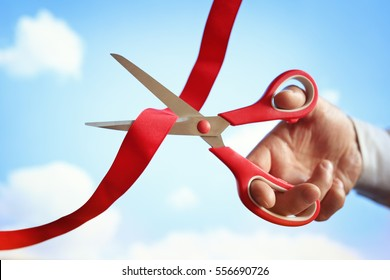 Businessman cutting a red ribbon with a pair of scissors at opening ceremony