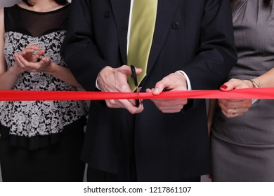 Businessman cutting red ribbon while other people next to him are clapping hands