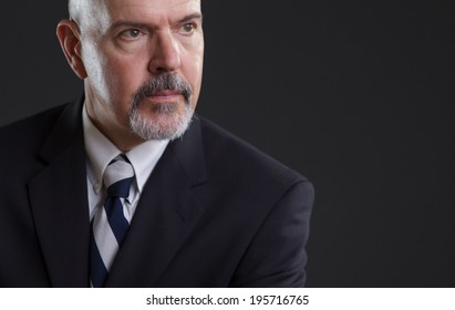 businessman in dark blue suit looking serious, tight cropping