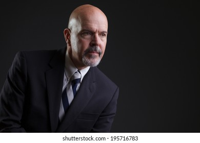 businessman in dark blue suit looking serious, looking away