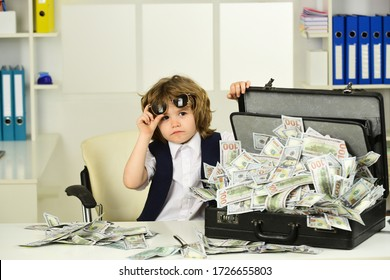 Businessman, deal and money. The boy makes an emotional face with sunglasses. Lots of cash at home. Financial security. Financial education for children.