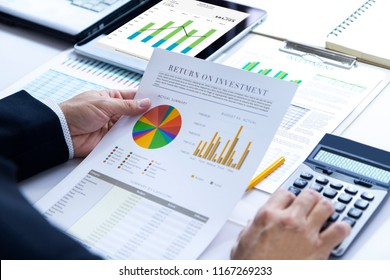 Businessman is deeply reviewing a financial report for a return on investment or investment risk analysis.