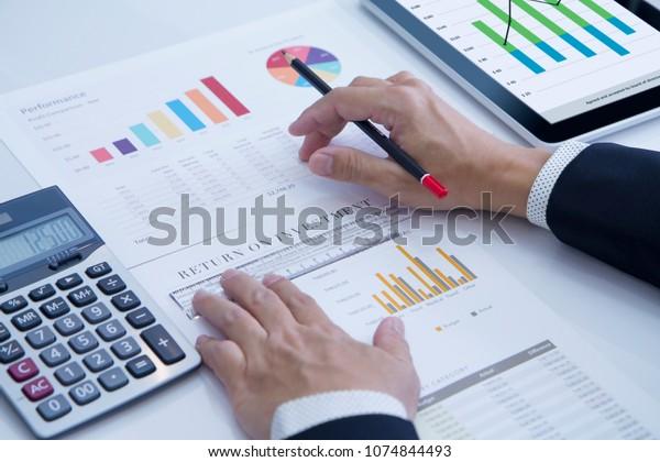 Businessman está revisando a fondo un informe financiero para un análisis del rendimiento de la inversión o del riesgo de inversión.