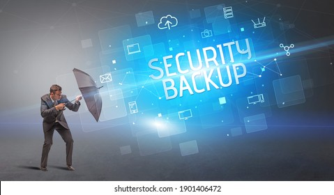 Businessman defending with umbrella from cyber attack and SECURITY BACKUP inscription, online security concept