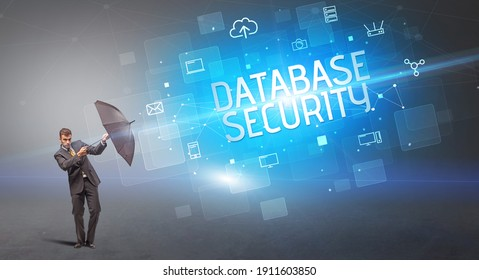 Businessman defending with umbrella from cyber attack and DATABASE SECURITY inscription, online security concept