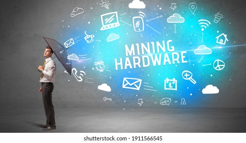 Businessman defending with umbrella from MINING HARDWARE inscription, modern technology concept
