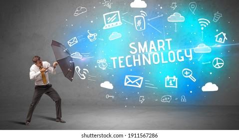 Businessman defending with umbrella from SMART TECHNOLOGY inscription, modern technology concept