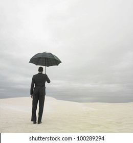 Businessman in the desert with an umbrella