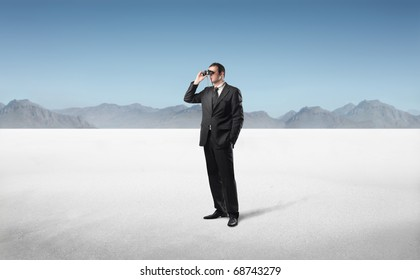 Businessman in a desert using binoculars
