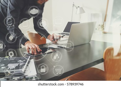 businessman or Designer using smart phone with laptop and digital tablet computer and document on desk in modern office with virtual interface graphic icons network diagram