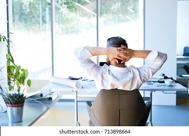 Businessman at the desk in his office resting.