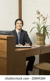 Businessman at desk smiling while typing at a computer. Vertically framed photo.