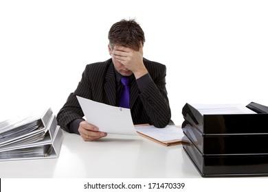 Businessman in despair behind his desk over white background