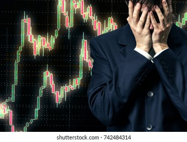 Businessman in despair on candlestick chart graphic background