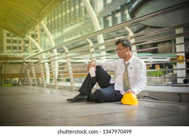 Businessman despair in white shirt with yellow engineer helmet sitting on pavement, Lonely man looking without hope - Image