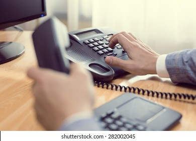 businessman dialing voip phone in the office, keyboard and monitor detail in the background with vintage color tone effect