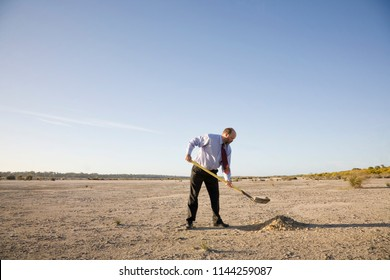 A businessman digging a hole, perhaps to bury his head in the sand. Concepts.