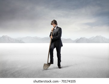 Businessman digging with a shovel in a desert