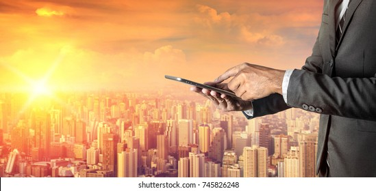 Businessman with digital tablet on city background