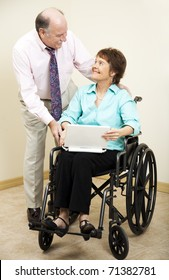 Businessman and disabled businesswoman.  She is using a laptop computer.