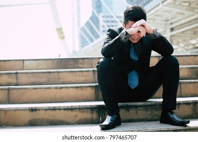 Businessman disappointment of being denied a job, he sat on the steps with hands on head.