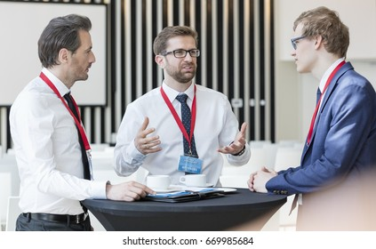 Businessman discussing with colleagues during coffee break in convention center