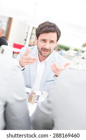 Businessman discussing with colleagues at sidewalk cafe