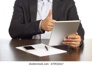 Businessman is discussing on video communication on tablet with business partners in office at desk isolated on white background. Successful businessman holds thumb up Business concept of partnerships