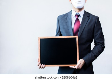 Businessman in disguise mask holding blackboard sign - ready to insert text